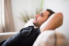 Homem da vista lateral que encontra-se e que relaxa no sofá em casa na sala de visitas fotografia de stock