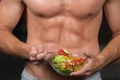 Homem dado forma e saudável do body building que guarda uma bacia de salada fresca, abdominal dado forma Imagem de Stock