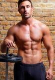 Homem dado forma músculo do corpo com pesos na parede de tijolo Fotos de Stock Royalty Free