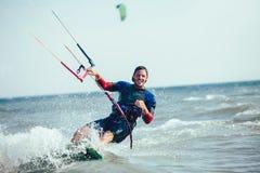 Homem das fotos da ação de Kitesurfing Kiteboarding entre ondas Foto de Stock