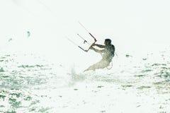 Homem das fotos da ação de Kitesurfing Kiteboarding entre ondas Imagens de Stock