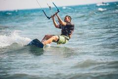 Homem das fotos da ação de Kitesurfing Kiteboarding entre ondas Fotografia de Stock