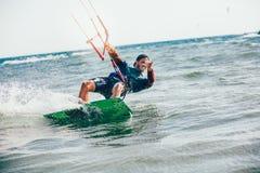 Homem das fotos da ação de Kitesurfing Kiteboarding entre ondas Imagem de Stock