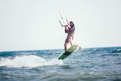 Homem das fotos da ação de Kitesurfing Kiteboarding entre ondas Imagens de Stock Royalty Free