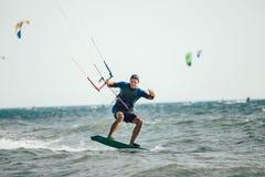 Homem das fotos da ação de Kitesurfing Kiteboarding entre ondas Fotos de Stock