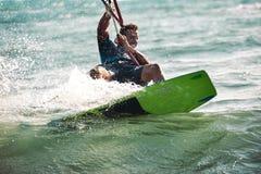 Homem das fotos da ação de Kitesurfing Kiteboarding entre ondas Imagem de Stock Royalty Free