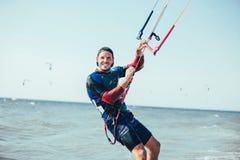 Homem das fotos da ação de Kitesurfing Kiteboarding entre ondas rapidamente Fotografia de Stock Royalty Free