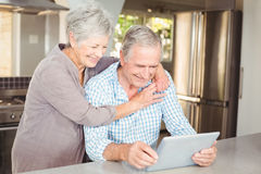 Homem de abraço da mulher superior feliz que usa a tabuleta Fotos de Stock