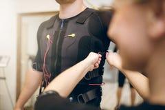 Homem de ajuda da mulher com colocação do terno do ems sobre foto de stock royalty free