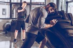 Homem de ajuda do instrutor que puxa o pneu ao exercitar no gym fotografia de stock royalty free