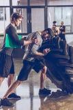 Homem de ajuda do instrutor que puxa o pneu ao exercitar no gym Fotos de Stock