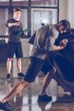 Homem de ajuda do instrutor que puxa o pneu ao exercitar no gym Imagem de Stock Royalty Free