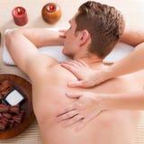 Homem de Andsome relaxado e que aprecia a massagem traseira foto de stock