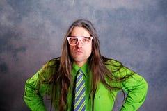 Homem de cabelos compridos, irritado em vidros verdes do rosa da camisa Imagens de Stock
