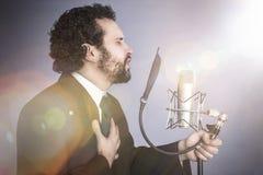 Homem de canto com terno e o microfone pretos Fotos de Stock Royalty Free