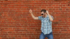 Homem de dança farpado novo feliz Emoção humana positiva, fundo da parede de tijolo video estoque