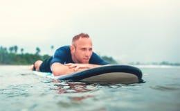Homem de descanso do surfista na placa Fotos de Stock