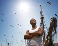 Homem de encontro ao mastro do barco fotos de stock royalty free