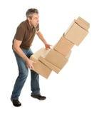 Homem de entrega com a pilha de queda de caixas Fotos de Stock Royalty Free