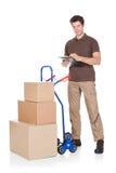Homem de entrega com prancheta e caixas Fotos de Stock Royalty Free