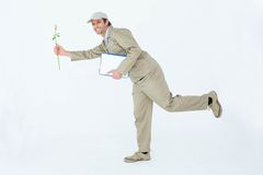 Homem de entrega feliz com a flor de oferecimento da prancheta foto de stock royalty free