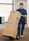 Homem de entrega na pilha de empurrão uniforme de caixas Fotografia de Stock