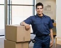 Homem de entrega no uniforme que levanta com a pilha de caixas Imagens de Stock