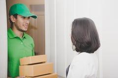 Homem de entrega no verde que entrega pacotes a uma porta da mulher fotografia de stock