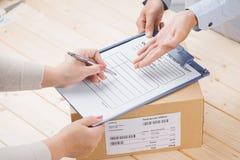 Homem de entrega que apresenta recebendo o formulário na estação de correios fotografia de stock