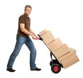 Homem de entrega que empurra o caminhão de mão e a pilha de caixas Fotografia de Stock