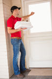 Homem de entrega que guarda a pizza ao bater na porta fotografia de stock