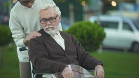 Homem de envelhecimento que senta-se na cadeira de rodas, neta que consola o, apoio da família video estoque