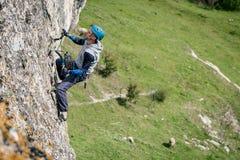 Homem de escalada em uma rocha imagem de stock royalty free