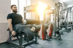 Homem de exercício farpado muscular atlético no gym moderno do esporte Aptidão, esporte, treinamento, conceito dos povos imagem de stock