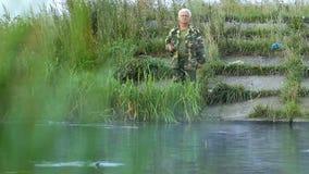 Homem de Fisher com os peixes de travamento da vara de pesca no lago video estoque