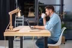 Homem de funcionamento duro agradável que come o café Fotografia de Stock Royalty Free