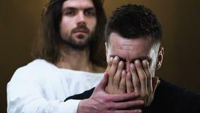 Homem de grito doente da cura de Jesus Christ, cara de fechamento com mãos, fundo escuro filme