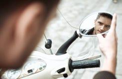 Homem de Handsomke que olha si mesmo no espelho da bicicleta Imagem de Stock Royalty Free