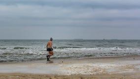 Homem de Icebathing na praia Báltico Foto de Stock