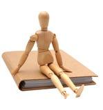 Homem de madeira que senta-se no caderno marrom fotografia de stock royalty free