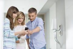 Homem de meia idade com as filhas que usam o telefone esperto em casa foto de stock