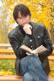 Homem de meia idade com um livro no parque imagem de stock