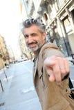 Homem de meia idade considerável na cidade que aponta o dedo imagem de stock royalty free