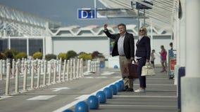 Homem de meia idade e aeroporto saindo fêmea e saudação de um táxi, viajando video estoque