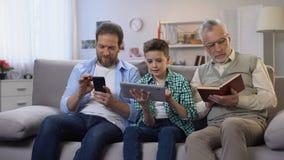 Homem de meia idade e dispositivos preteen do desdobramento do menino, livro de papel de envelhecimento da leitura do homem filme