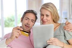 Homem de meia idade e mulher que compram em linha foto de stock royalty free