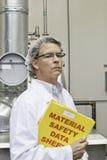 Homem de meia idade que guarda folhas de dados da fábrica foto de stock