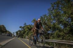 Homem de meia idade que veste um terno e que dá um ciclo na cidade de Bourgas/Bulgária/10 11 2017/ imagens de stock