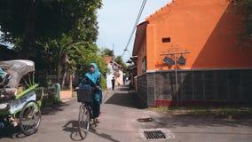 Homem de montada do trishaw da mulher na rua em Pekalongan video estoque