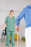 Homem de motivação do fisioterapeuta com muletas Imagens de Stock Royalty Free